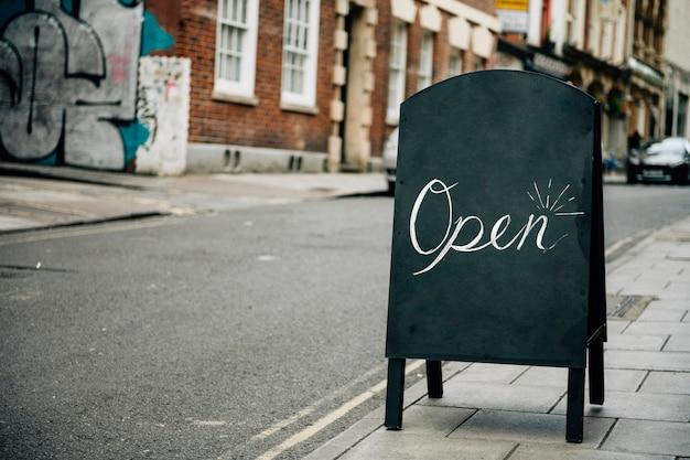Marco de pie de una señal abierta para los negocios