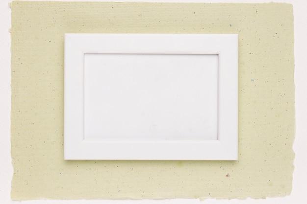 Marco pintado de blanco sobre papel verde menta