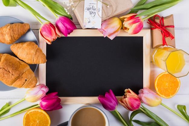 Marco de pizarra alrededor de tulipanes y desayuno