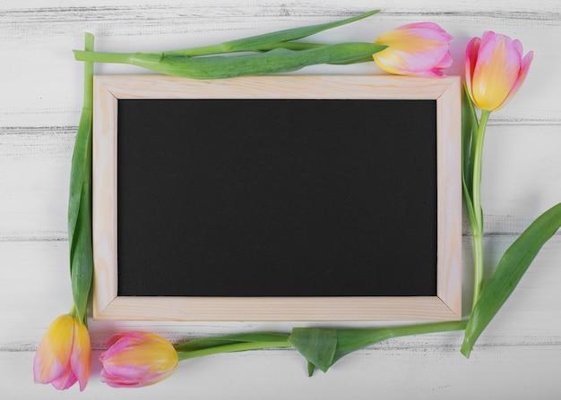 Marco de pizarra alrededor de tulipanes