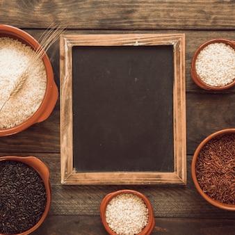 Marco de pizarra con cuencos de arroz diferente en la mesa de madera