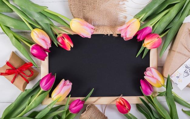 Marco de pizarra decorado con tulipanes y cajas de regalo.