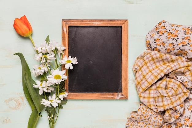 Marco de pizarra con flores y chales.