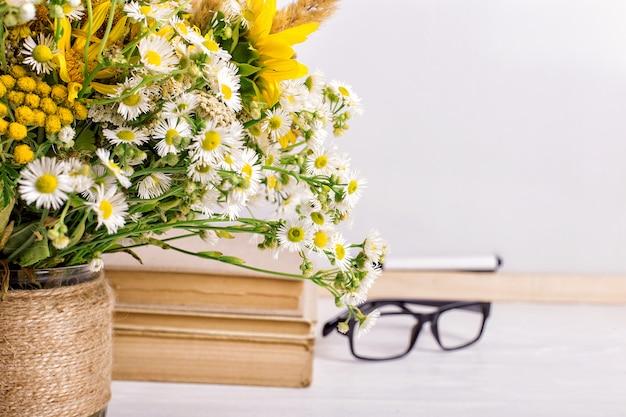 Marco de pizarra de madera y jarrón bouquet en mesa vacía