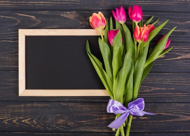 Marco de pizarra con ramo de tulipanes