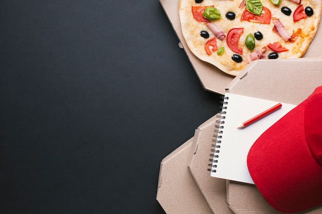Marco de pizza de vista superior con gorra roja y cuaderno
