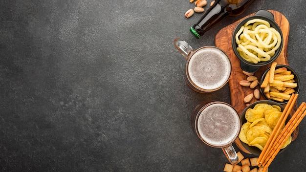 Marco plano con cerveza y bocadillos.