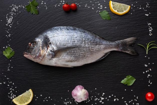 Marco plano de condimentos con pescado en el centro