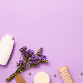 Marco plano laico con botella blanca y flor lila