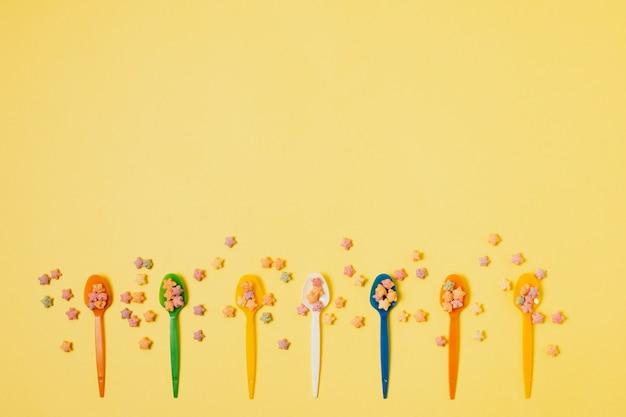 Marco plano laico con cucharas sobre fondo amarillo