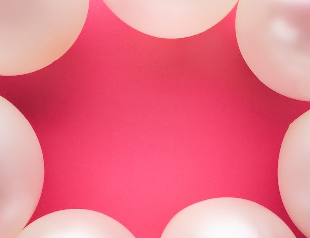 Marco plano laico con globos y fondo rosa