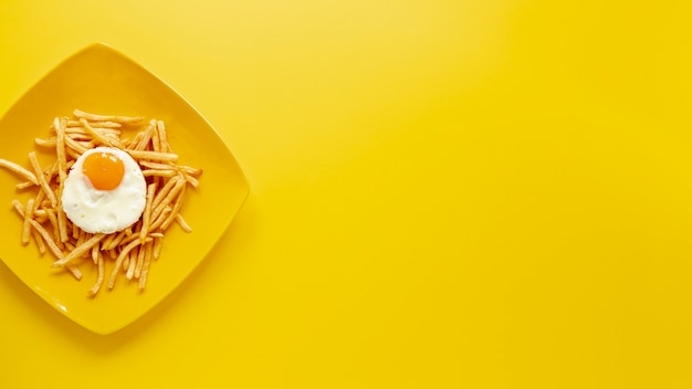 Marco plano laico con huevo y papas fritas en un plato