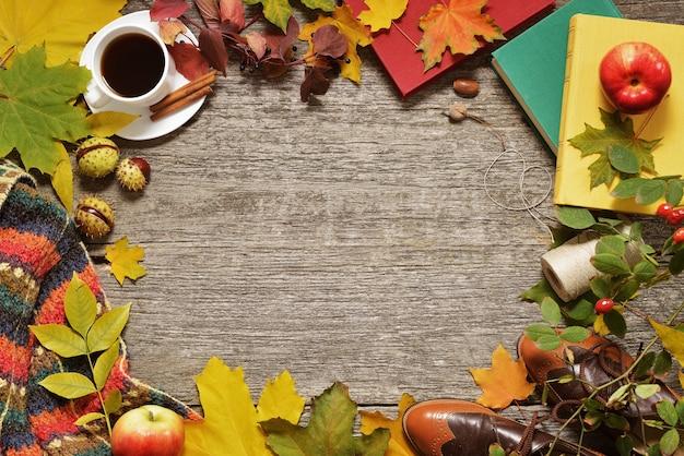 Marco plano laico de otoño rojo, hojas verdes y amarillas, bellotas y manzanas sobre un fondo de madera vintage.