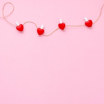 Marco plano laico con pequeños corazones y fondo rosa