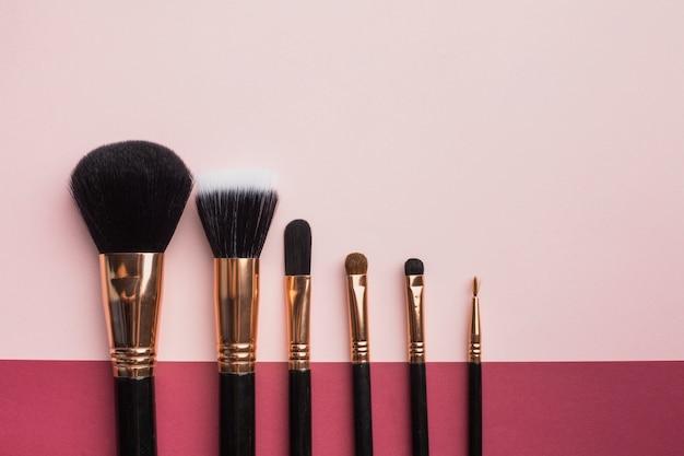 Marco plano laico con pinceles de maquillaje y fondo rosa