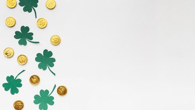 Marco plano de monedas y tréboles