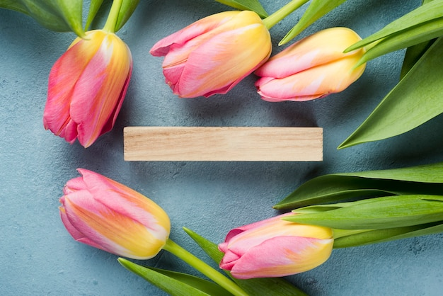Marco plano de tulipanes con etiqueta de madera