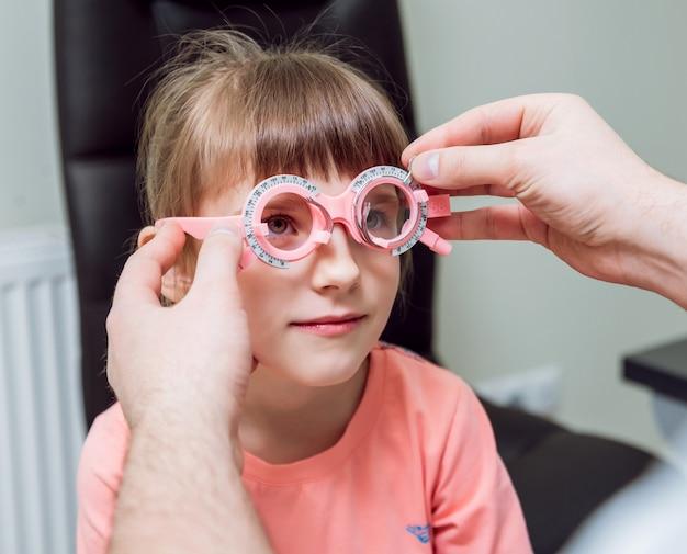Marco de prueba anteojos recetados para un niño. hipermetropía del niño. la miopía del niño. la miopía infantil. la hipermetropía del niño. corrección de ametropía con gafas.