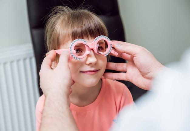 Marco de prueba anteojos recetados para un niño. hipermetropía del niño. la miopía del niño. la miopía del niño. la hipermetropía del niño. corrección de ametropía con gafas.