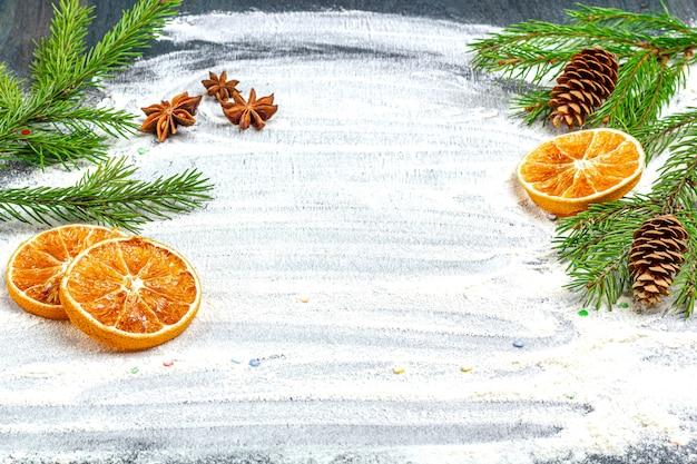 Marco de ramas de abeto, conos, anís estrellado, canela y naranjas secas sobre un fondo de harina.