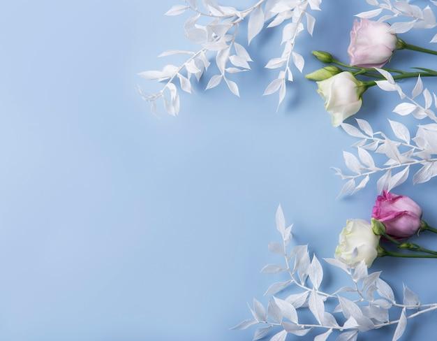Marco de ramas blancas con hojas y flores sobre un fondo azul.