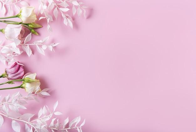 Marco de ramas blancas con hojas y flores sobre un fondo rosa