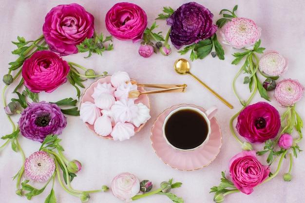 Un marco de ranunculus y merengue, una taza de café.