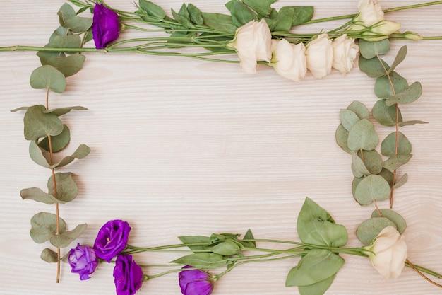 Marco realizado con las flores blancas y moradas de eustoma sobre fondo de madera.