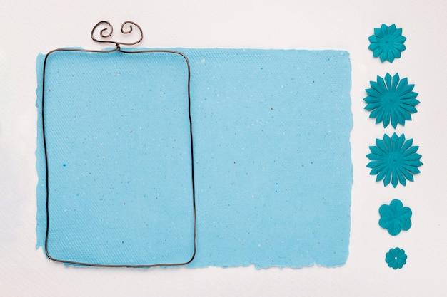 Marco rectangular cerca del papel azul decorado con flores sobre fondo blanco.