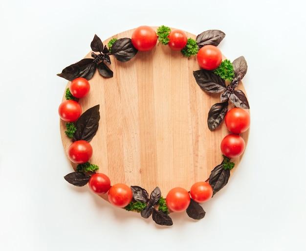 Marco redondeado de tomates cherry, hojas de albahaca morada y perejil