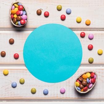 Marco redondo azul rodeado de coloridas gemas en tablero de madera