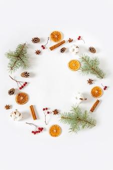Marco redondo, corona de ramas de abeto, naranjas secas, palitos de canela, anís estrellado, flores de algodón.