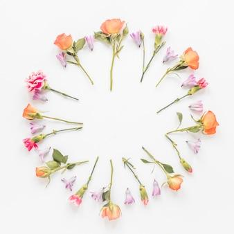 Marco redondo de diferentes flores en la mesa.