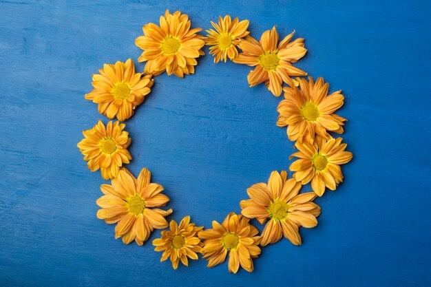 Marco redondo de flores sobre un fondo azul. crisantemos naranjas con espacio de copia