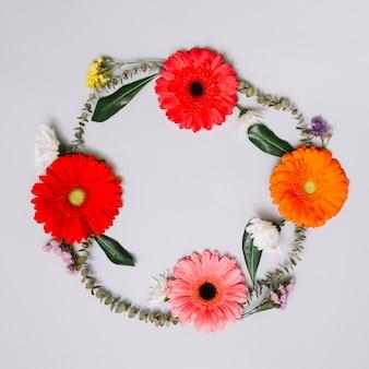 Marco redondo hecho de flores y capullos y hojas.