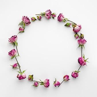Marco redondo o corona hecha de rosas rosadas secas sobre blanco