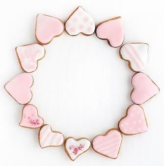 Marco redondo de pan de jengibre en forma de corazón de diferentes tamaños en esmalte blanco y rosa sobre un fondo blanco. espacio para texto.