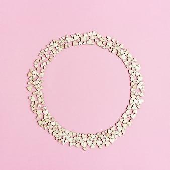 Marco redondo de pequeños corazones de madera sobre papel rosa. fondo de vacaciones
