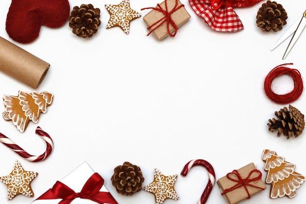 Marco de regalos de navidad sobre un fondo blanco, cajas de regalo de caramelos de navidad, pan de jengibre y pino