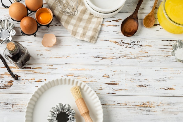 Marco de repostería, ingredientes, utensilios de cocina en madera rústica