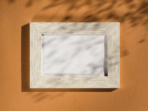 Marco de retrato de madera sobre un fondo beige cubierto con sombras de hojas