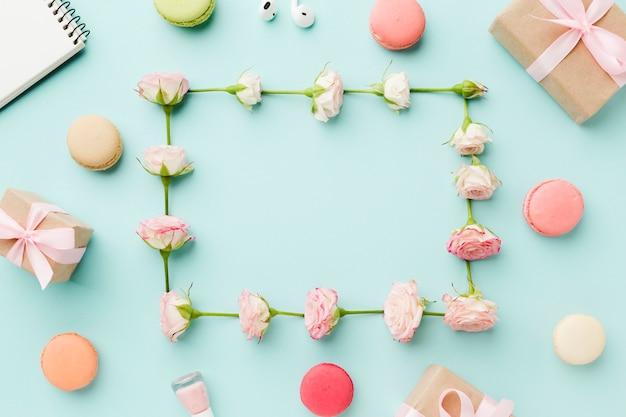Marco de rosas rodeado de dulces y regalos.