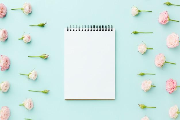 Marco de rosas rosadas con bloc de notas vacío