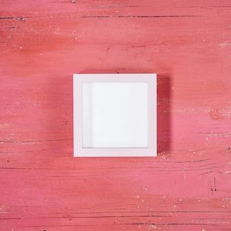 Marco sobre fondo de madera rosa claro
