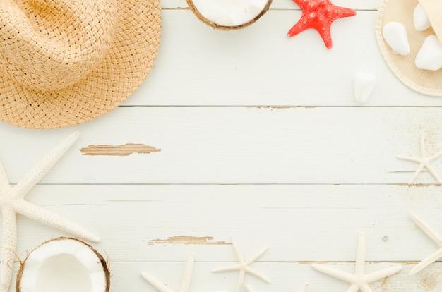 Marco de sombrero de paja, estrellas de mar y cocos.