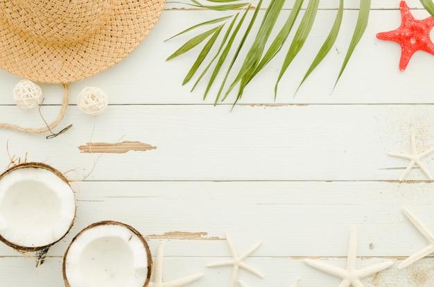 Marco de sombrero de paja, estrellas de mar y hoja de palma.