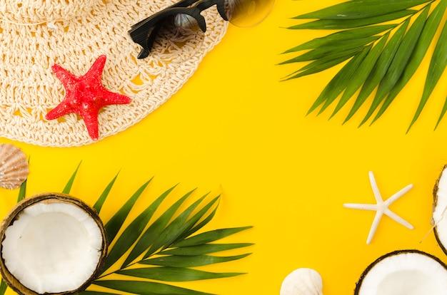 Marco de sombrero de paja, hojas de palmera y cocos.