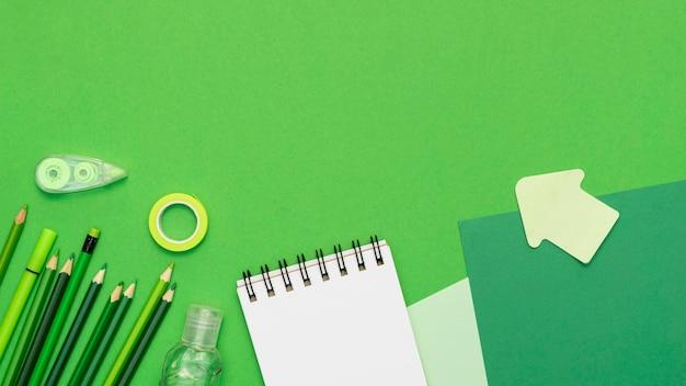 Marco con suministros en fondo verde
