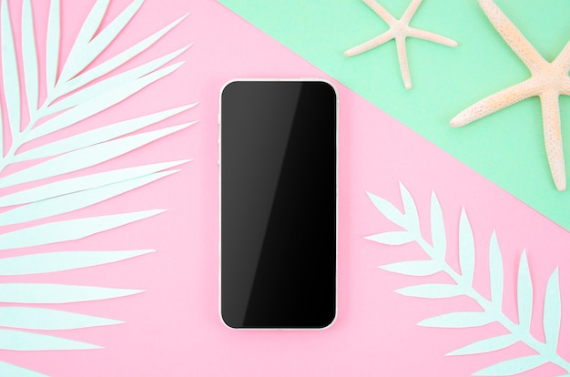 Marco del teléfono inteligente con pantalla en blanco sobre fondo de pastel pop con hojas de palma de papel