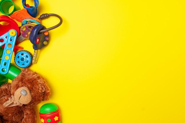 Marco para el texto. la vista superior de la construcción multicolor del juguete de los niños bloquea ladrillos en fondo amarillo
